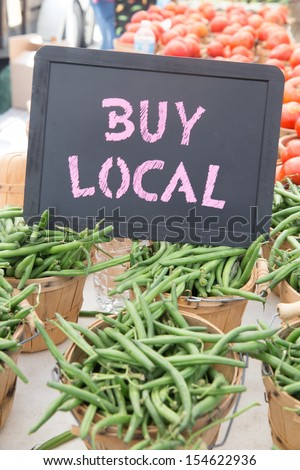 Locally Grown Green Beans and Tomatoes in Brown Baskets For Sale at the Farmers Market - stock photo