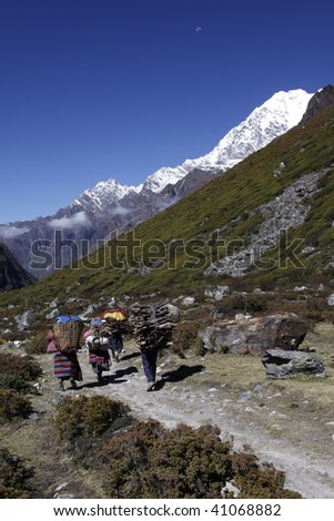 Locals carry wood and supplies in the mountains of Nepal. - stock photo