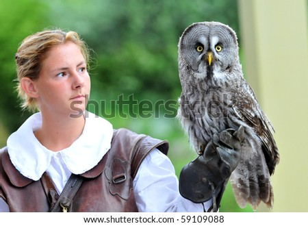 LOCARNO, SWITZERLAND - AUGUST 13: Female falconer holds a great grey owl at the Falconeria demonstration  August 13, 2010 in Locarno Switzerland - stock photo