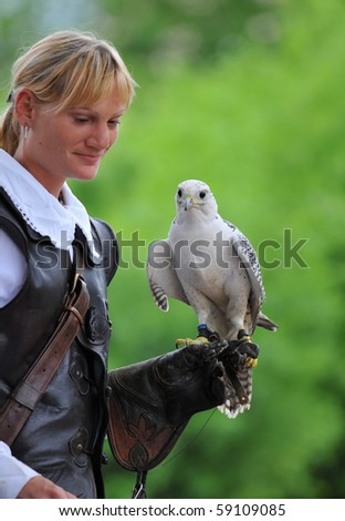 LOCARNO, SWITZERLAND - AUGUST 13: Female falconer holds a gyrfalcon at the Falconeria demonstration  August 13, 2010 in Locarno Switzerland - stock photo