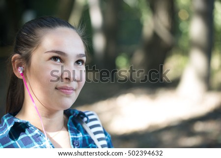 Location shot of a teen girl on a country road in the fall with a backpack waiting for the school bus