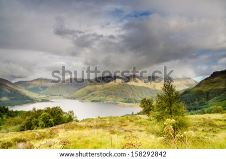 Loch Duich and Five Sisters / The end of Loch Duich with the Five Sisters peaks in cloud and hint of a rainbow - stock photo
