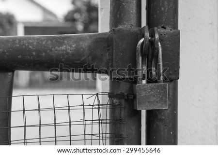 locked rusty silver padlock on house gate