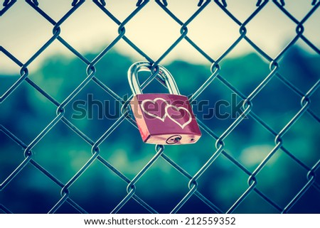 Lockers symbolizing love forever on the fence with vintage style - stock photo