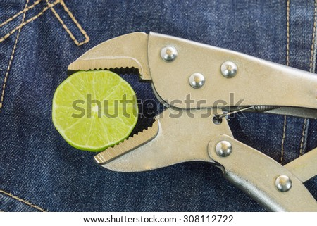 locking Pliers and lime put on jeans background. - stock photo