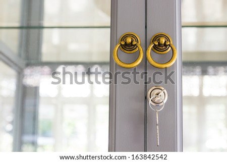 Locking up or unlocking door with key - stock photo