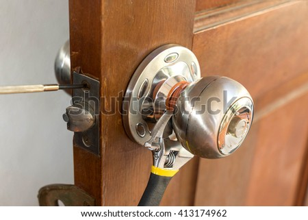 locksmith on wood door with screwdriver for repair or fix silver knob   - can use to web template about home service - stock photo