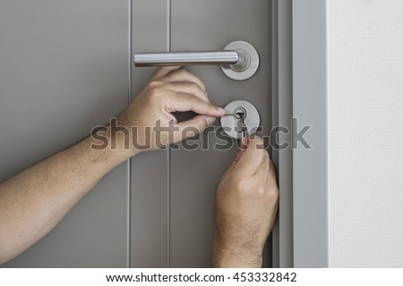 locksmith try to fix a key lock door for open it by screwdriver and tools - can use to display or montage on product - stock photo