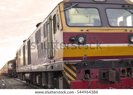 LOCOMOTIVE TRAIN IN THAILAND WITH GOLDEN CLOUD BACKGROUND, SOFT FOCUS.
