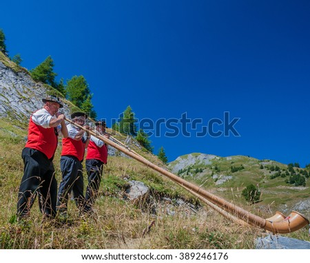 Lodging of Him Cottage of August, by Ovronnaz village, Valais, Martigny-August 23, 2009: A band of three Swiss horn players entertain the guests at the lodge during a Fondue party, Switzerland  - stock photo