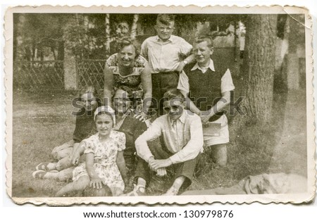LODZ, POLAND - CIRCA 1959: a big unidentified three-generation family poses for a photo in the garden in summer circa 1959 in Lodz, Poland