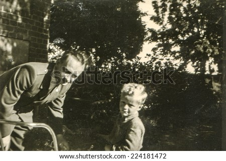 LODZ, POLAND, CIRCA AUGUST 1953: Vintage photo of father with little son - stock photo