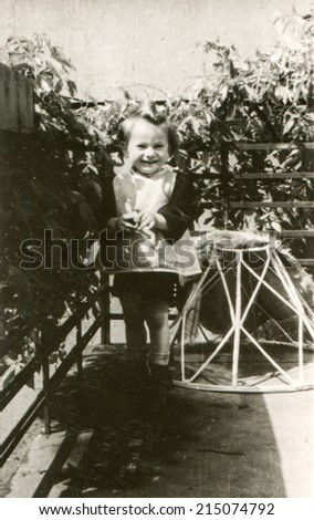 LODZ, POLAND, CIRCA FIFTIES: Vintage photo of little girl on balcony