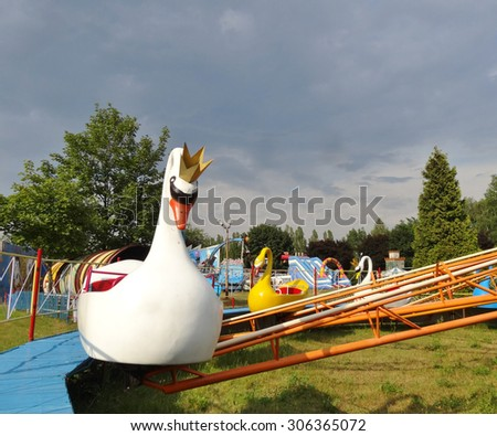"LODZ,POLAND - JULY 6,2014:Children's carousel - swans - ""Funfair"" in Lodz - stock photo"