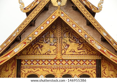 LOEI,THAILAND- APRIL 14 : Ancient Thai art on roof church made of teak wood age of about 400 years at Wat Sri Pho Chai temple on April 14,2013 in Nahae District,Loei Province,Northeast of Thailand.
