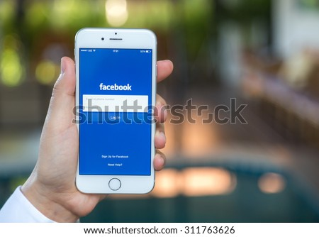 Loei, Thailand - August 12, 2015: Hand holding Iphone with mobile application for Facebook on the screen - stock photo
