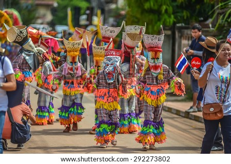 "Loei, Thailand - June 27, 2015 : People are dressing with colorful clothes and put the hand made mask which made from wood or threshing bamboo in ghost mask festival or ""Phi Ta Khon"""