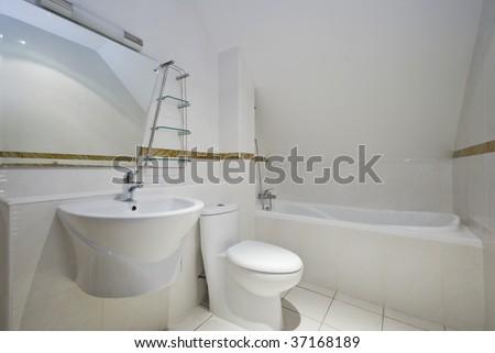 loft bathroom with angled ceiling bath tub toilet and sink - stock photo