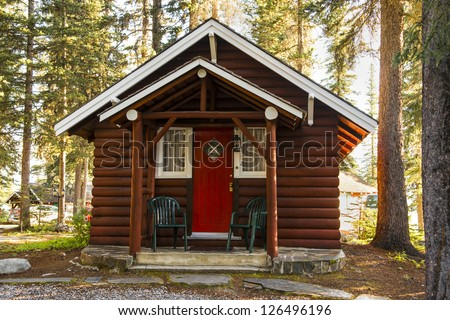 Log cabin in woodland setting - stock photo