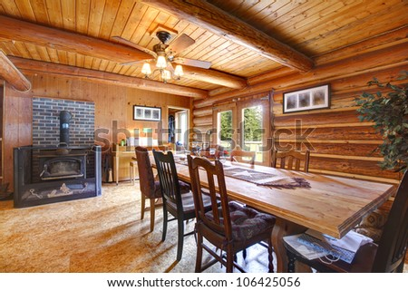 Log cabin rustic living room with large table and stove. - stock photo