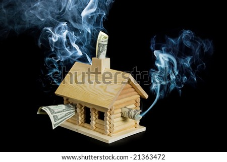Log cabin stuffed with money with smoke rising from it. Isolated on a black background. - stock photo