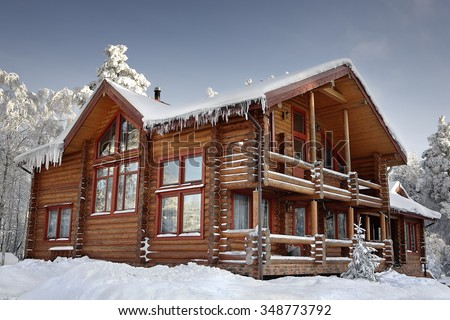 Log cabin with large windows, balcony and porch, modern house design, snowy winter, sunny day. - stock photo