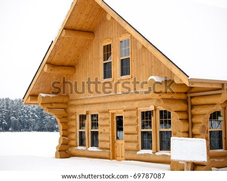 Log house covered in snow during winter - stock photo
