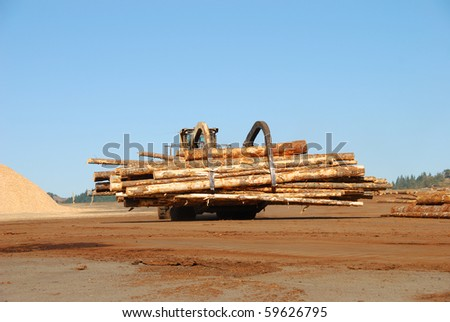 Log Loader working the log yard at a lumber processing mill in the Winchester area of Roseburg Oregon.  This mill specializes in small logs. - stock photo