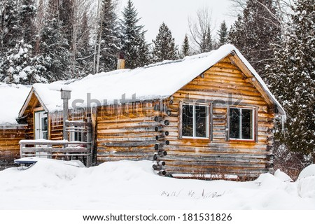 Log Wood Chalet in Quebec, Canada during a cold winter day. - stock photo