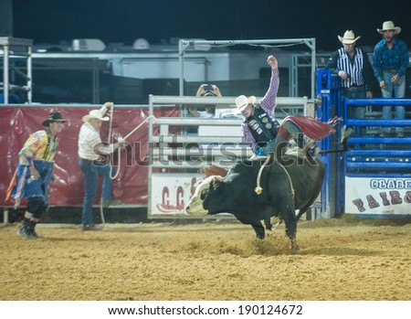 LOGANDALE , NEVADA - APRIL 10 : Cowboy Participating in a Bull riding Competition at the Clark County Fair and Rodeo a Professional Rodeo held in Logandale Nevada , USA on April 10 2014  - stock photo