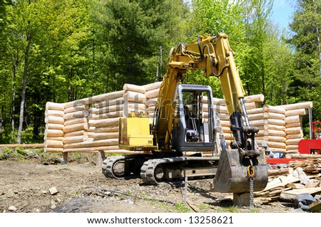 Loghouse under construction with an excavator in front of it - stock photo