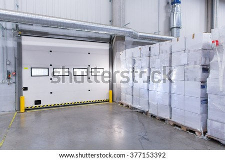 logistic, storage, shipment, industry and manufacturing concept - warehouse door or gate and cargo boxes - stock photo