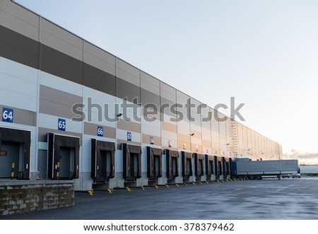 logistic, storage, shipment, transportation and loading concept - warehouse gates and truck loading - stock photo