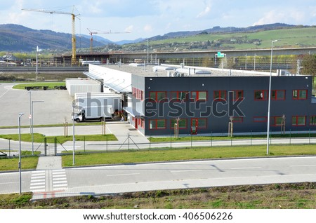 Logistics center, freight is uncharged from van. Tower cranes in background - stock photo