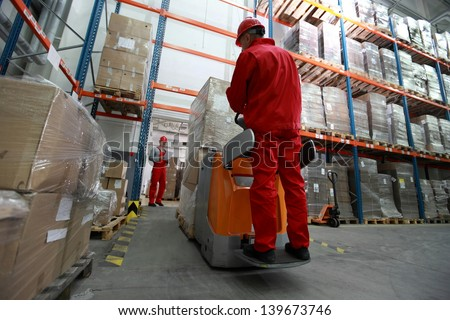 logistics - Goods delivery - two workers working in storehouse with forklift loader - stock photo