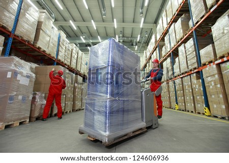 logistics - management of the flow of resources  - two workers in uniforms and safety helmets working in storehouse - stock photo