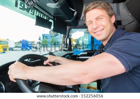 Logistics - proud driver or forwarder in drivers cap of truck and trailer, on a transshipment point - stock photo