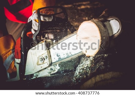 Logs Cutting Wood Cutter Closeup Photo. Gasoline Wood Cutter in Action. - stock photo