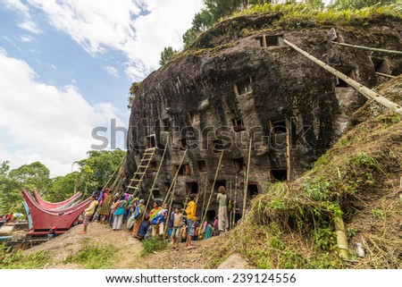 """Lokomata, Indonesia - September 9, 2014: Open graves in a cliff with local people attending the ceremony of cleaning corpses (""""Manene""""), held once in 5 or 10 years in Tana Toraja, South Sulawesi. - stock photo"""