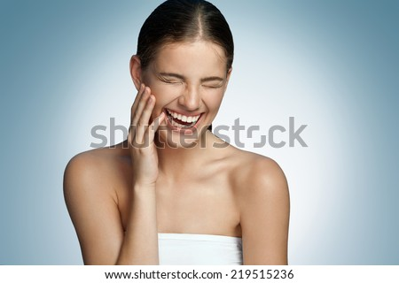 LOL (laughing out loud, laugh out loud, lots of laughs) / portrait of a young beautiful brunette girl laughing on blue background  - stock photo