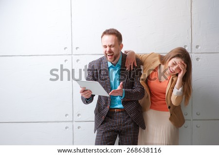 LOL! Watching funny video or reading a joke. Creative work and technology. Young man and woman using tablet computer and laughing against white wall. - stock photo
