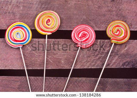 lollipop candies on wood background - stock photo