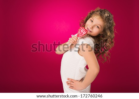 Lollipop. Heart. Candy. Little girl with lollipop in her hand on red background/ Studio - stock photo