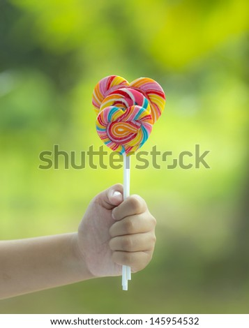 Lollipop in hand on nature background - stock photo