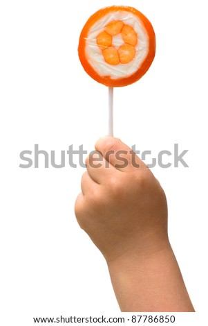 lollipop in the hand of a child on white background