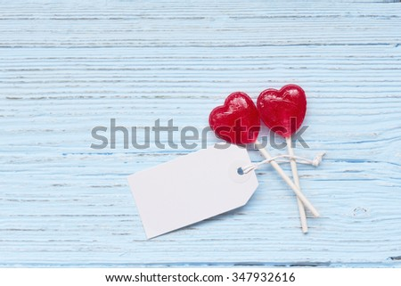 Lolly pop hearts  with a tag on a wooden background - stock photo