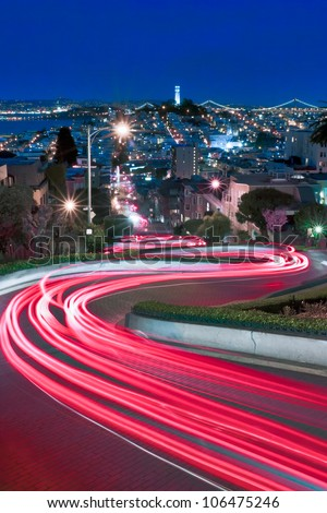 Lombard Street, one of the more famous of San Francisco, California is spiced up by some late night tourists and a long exposure. - stock photo
