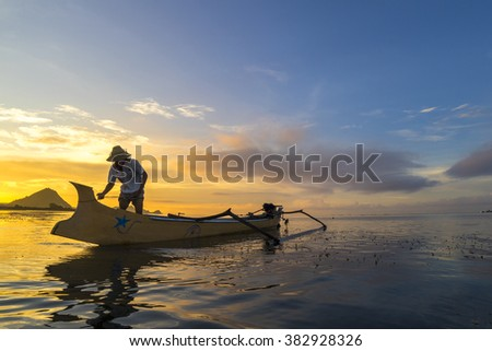 LOMBOK, INDONESIA - FEBRUARY 23, 2016: Unidentified fisherman ready to work in the boat early morning during sunrise moment. Fishing is the main occupation for the villagers. - stock photo