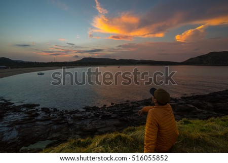 LOMBOK, INDONESIA - 16th SEPTEMBER 2016; A traveller looking into sunrise over Tanjung Ann beach in Lombok island, Indonesia. Tanjung Ann is one of famous place for tourist and traveller.