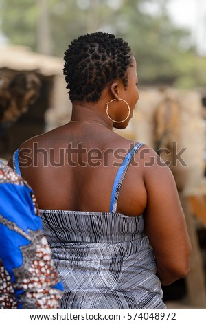 LOME, TOGO - Jan 9, 2017: Unidentified Togolese woman in big earing from behind at the Lome fetish market. Togo people suffer of poverty due to the bad economy